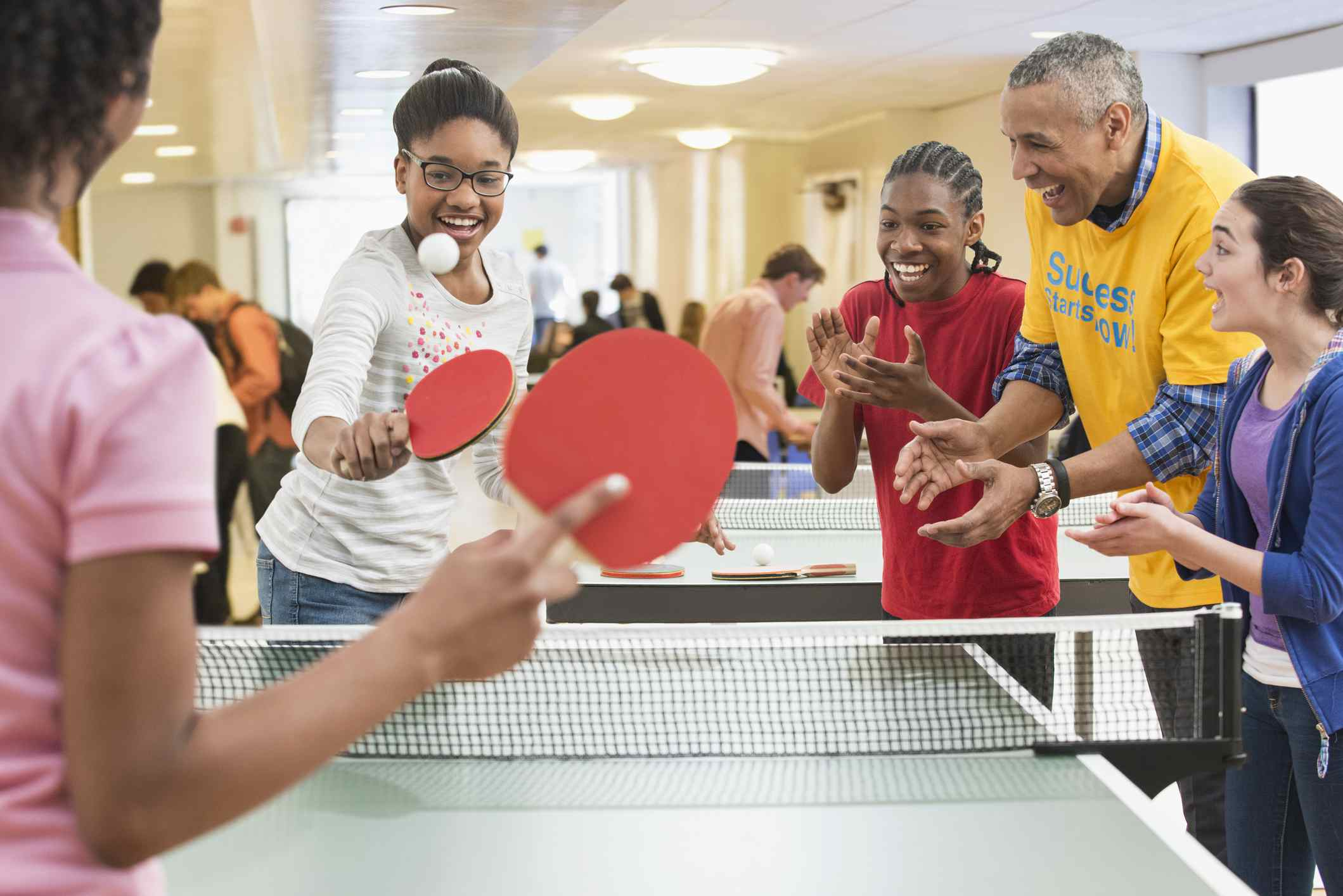 Group of kids and adult playing ping pong