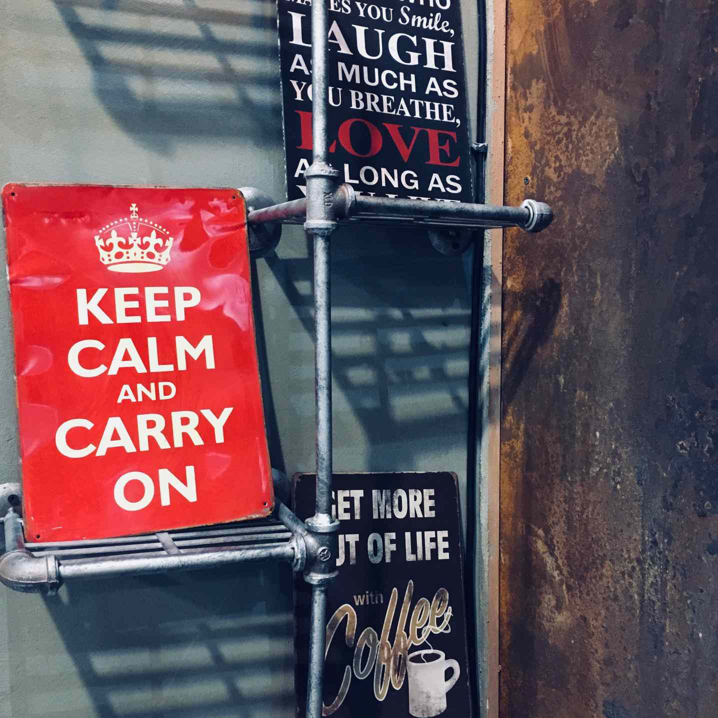 Red Keep Calm and Carry On sign on a shelf with other signage.