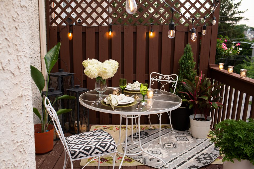Tiny balcony decorated as a retreat with hanging string lights, small patio furniture and garden plants
