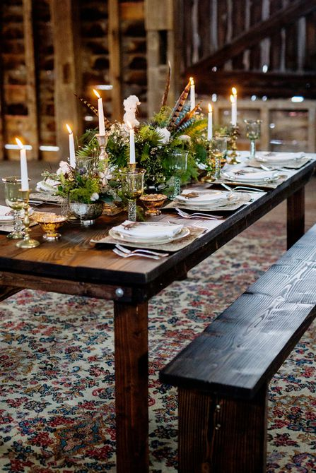 Centro de mesa de boda de invierno de vegetación y plumas caprichosas