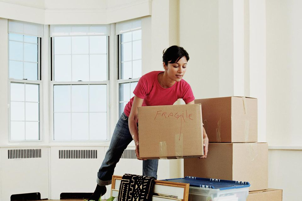 Young woman placing box on stack of belongings in apartment
