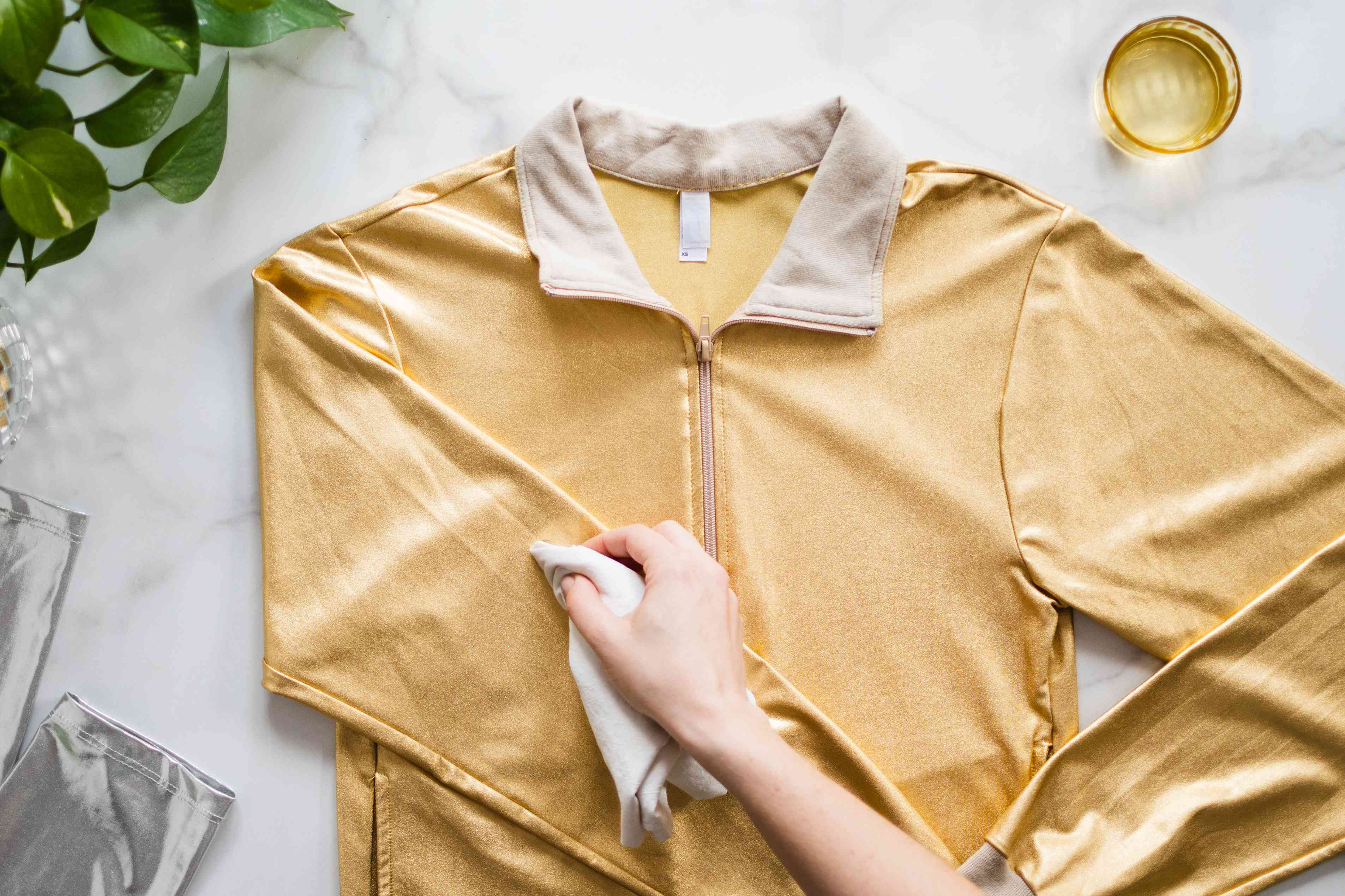 Stain blotted by white towel on left sleeve of yellow metallic jacket