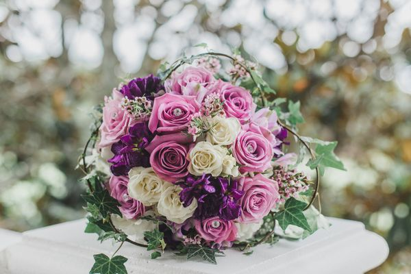 Pink and white roses round bride's bouquet outdoors on white Pilar with bokeh background