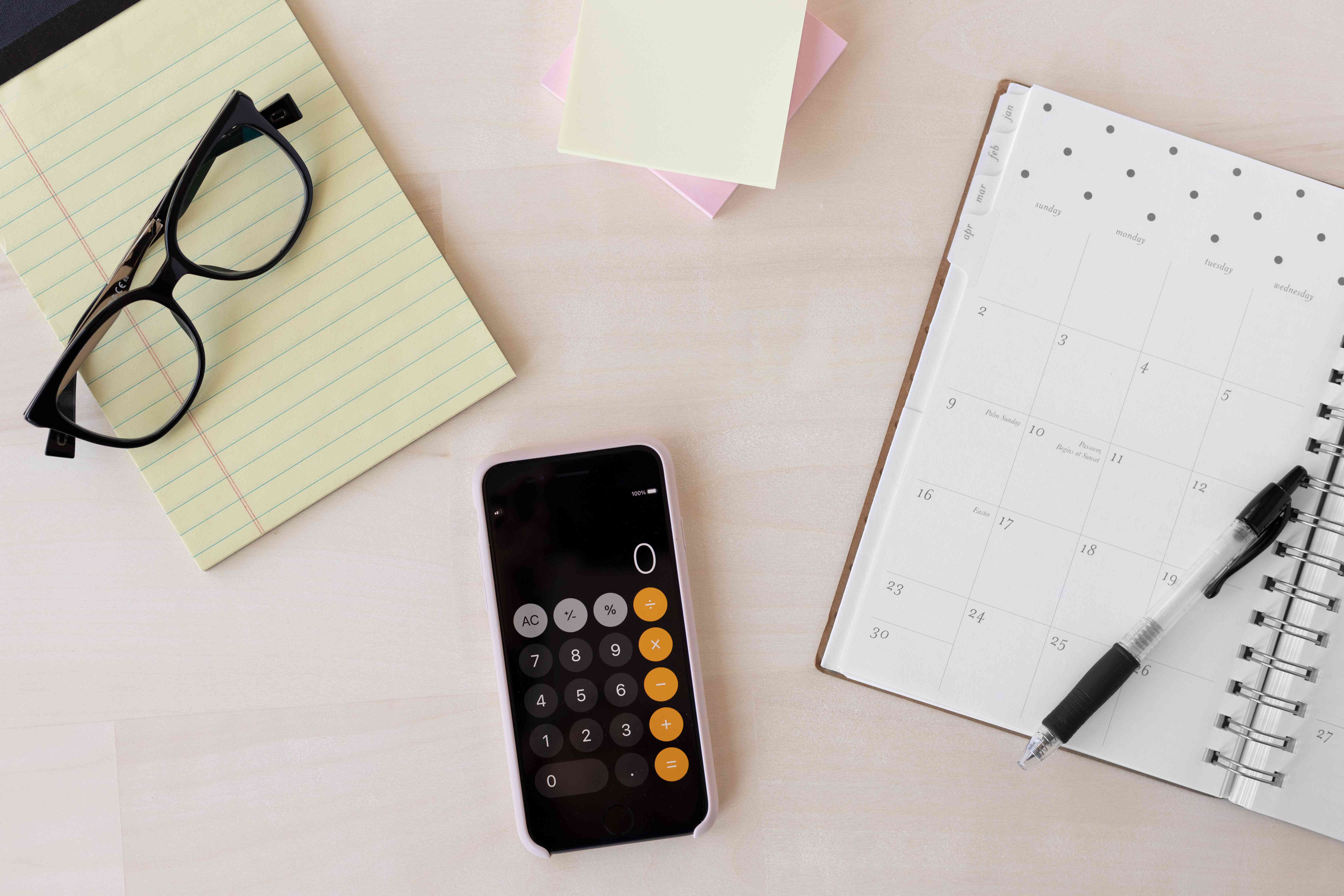Glasses on notepad with open calendar organizer, phone calculator and sticky notes