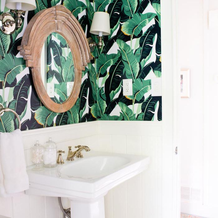 Bathroom with tropical wallpaper, with white sink and mirror