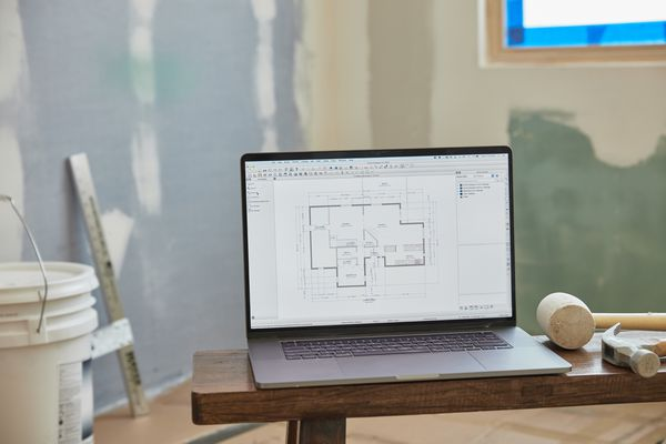 House floor-plan on computer in middle of room being renovated