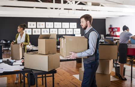 young man carrying a packed moving box in an office