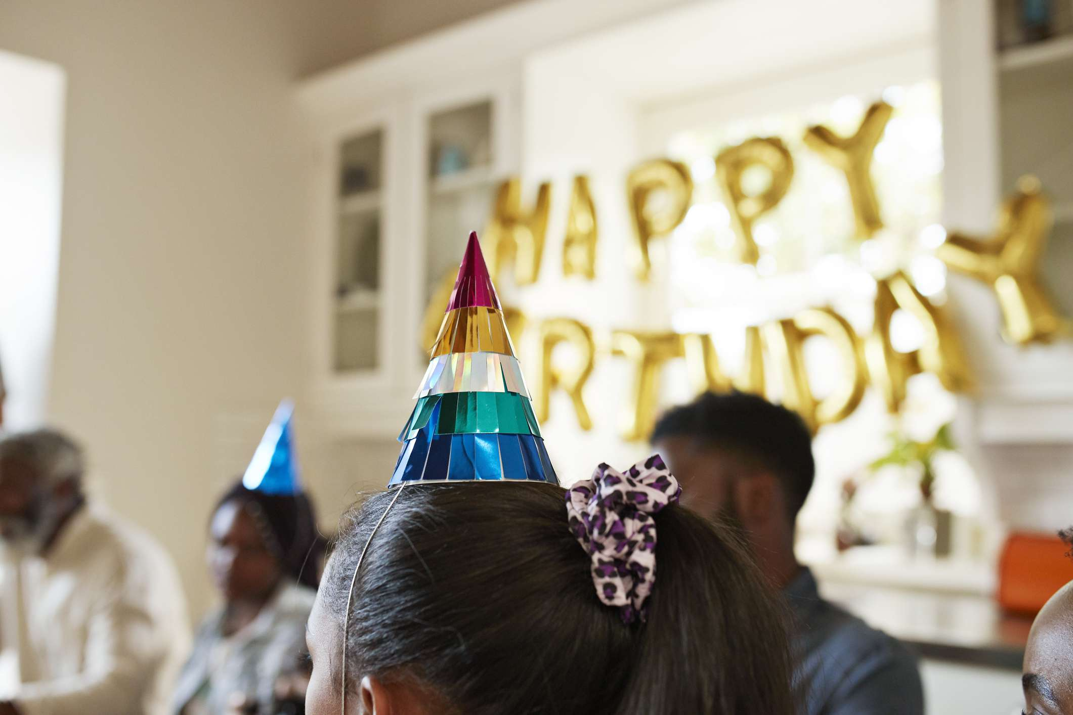 People wearing party hats at a birthday party.