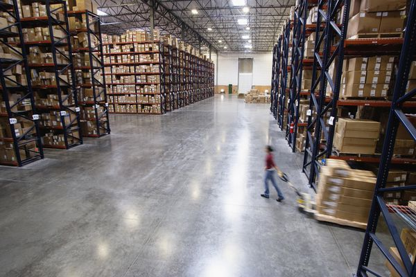 Female worker pulling boxes on hand cart in warehouse