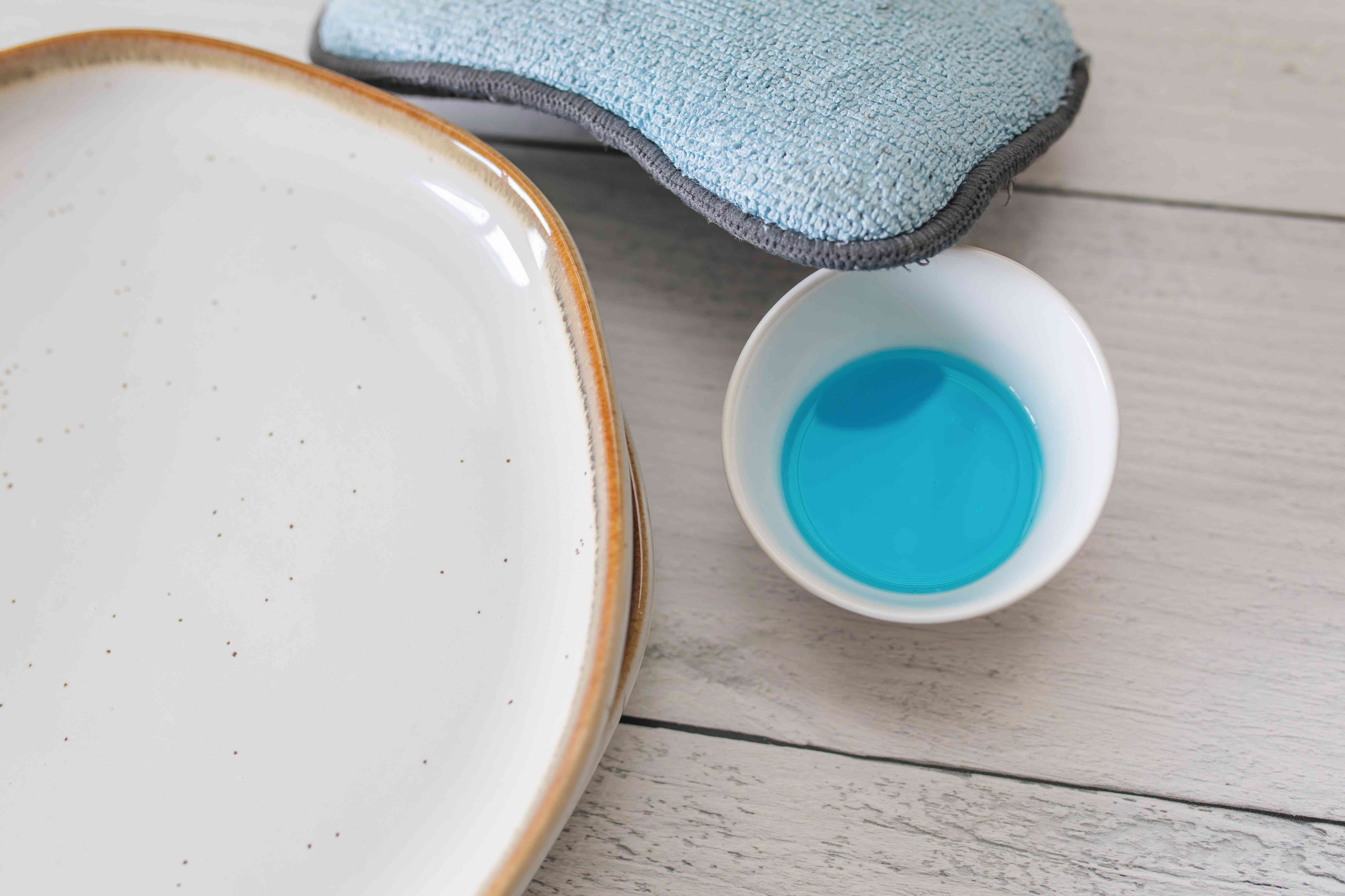 small cup of dish soap next to plates