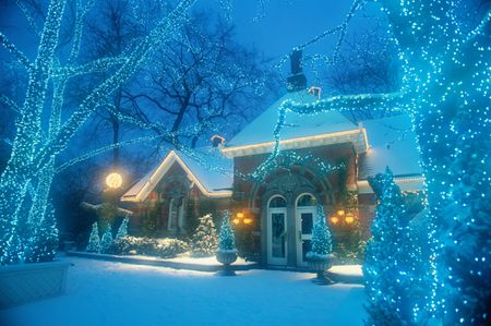 winter scene at nighttime with snow christmas lights and house