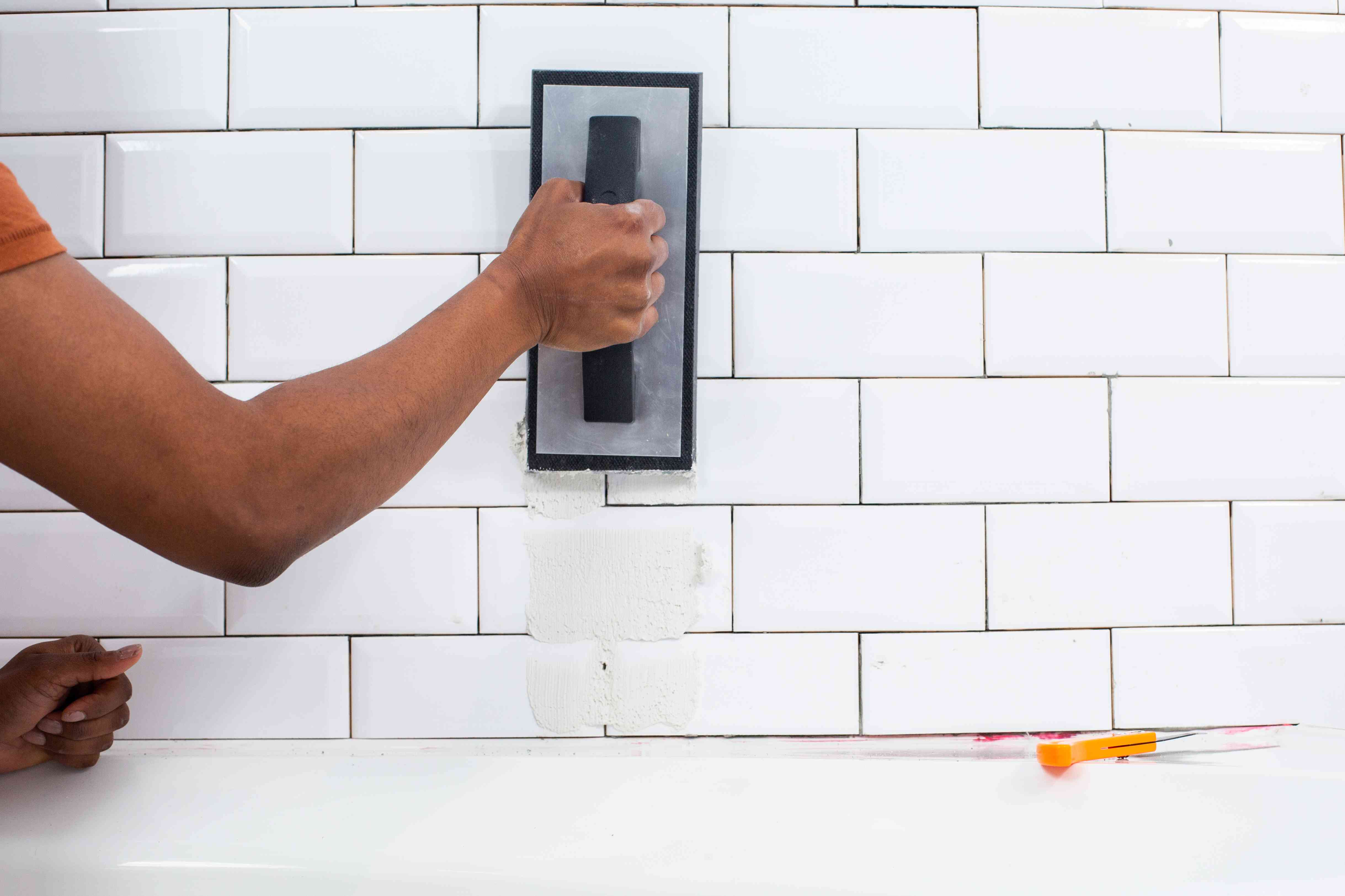 Grout float filling white bathroom wall tiles with grout
