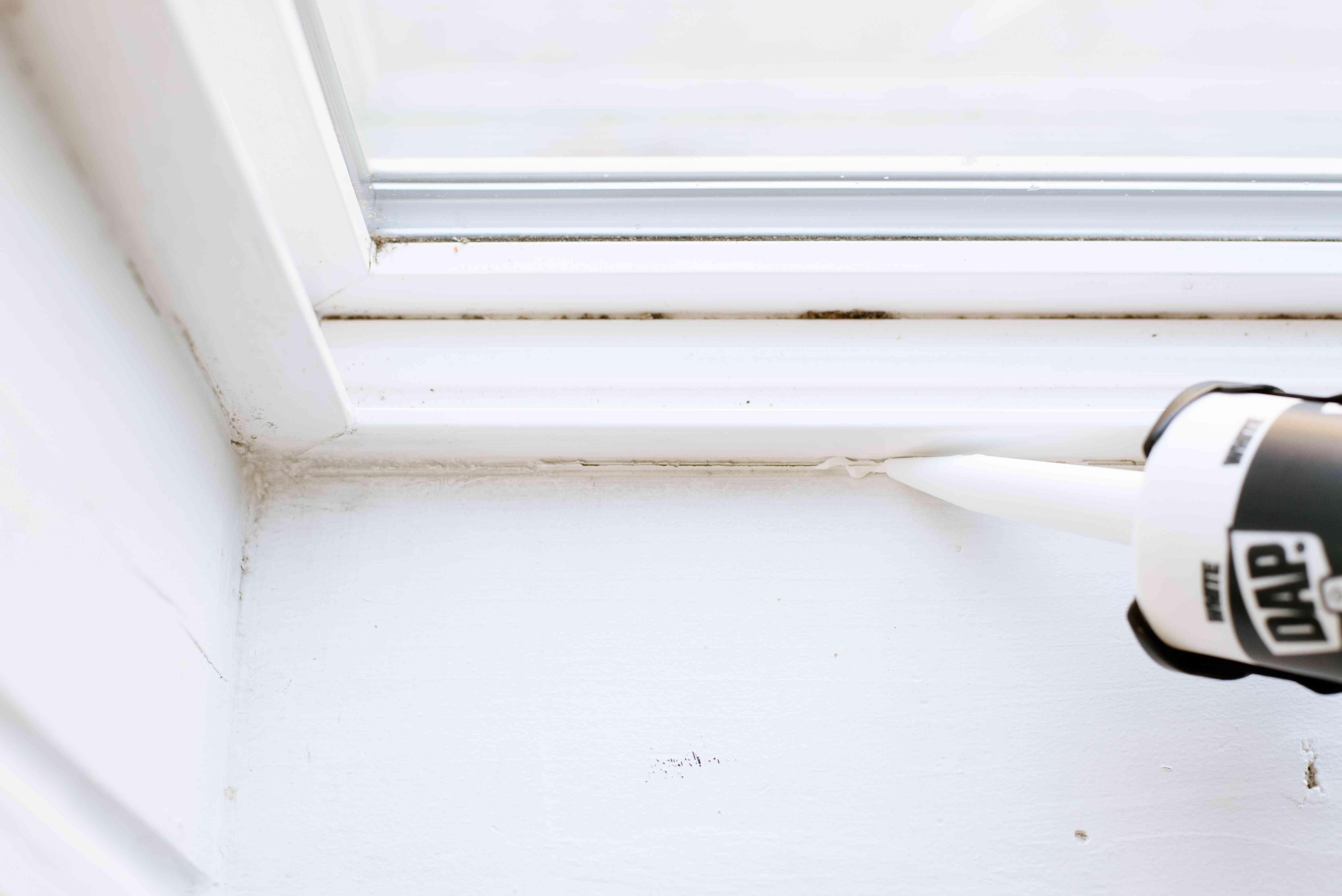 adding caulk to the window