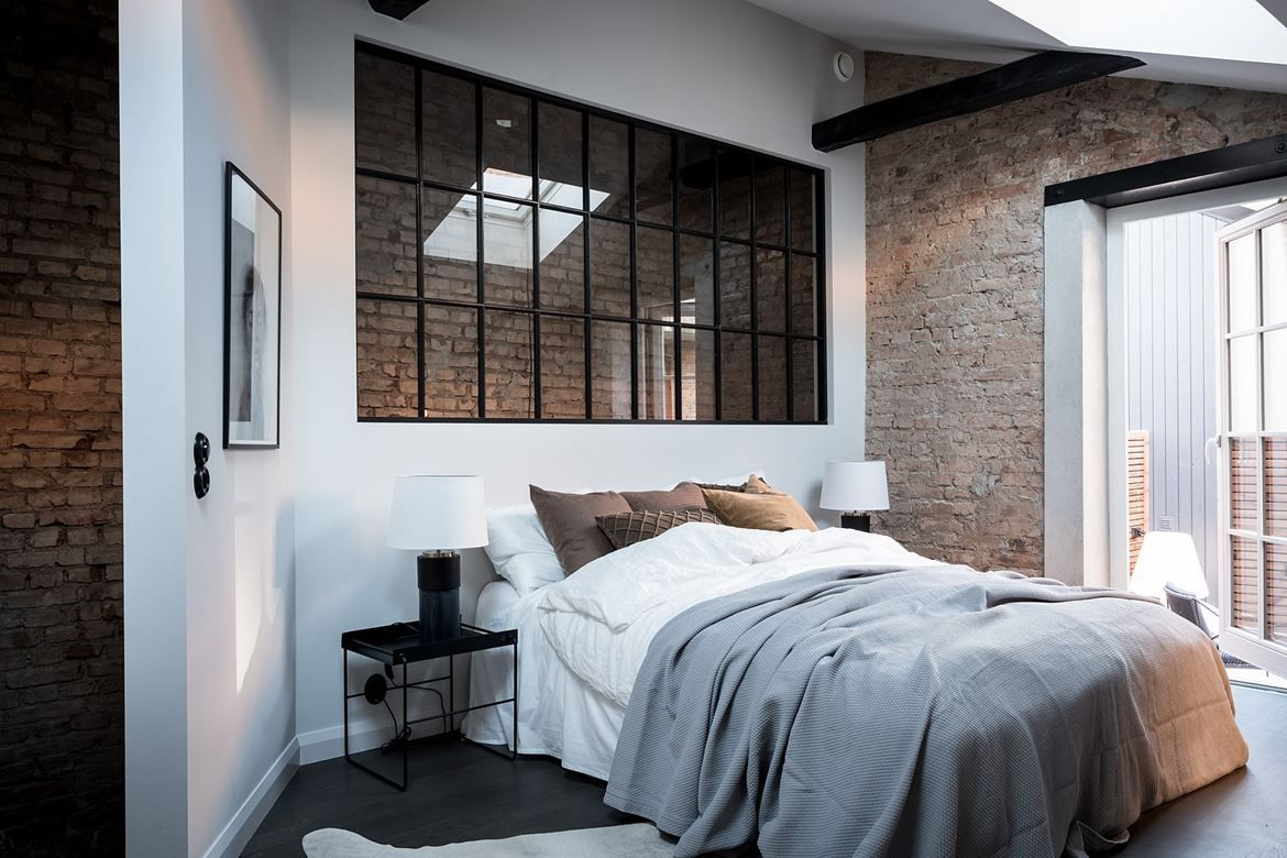 bedroom with interior windows and brick wall