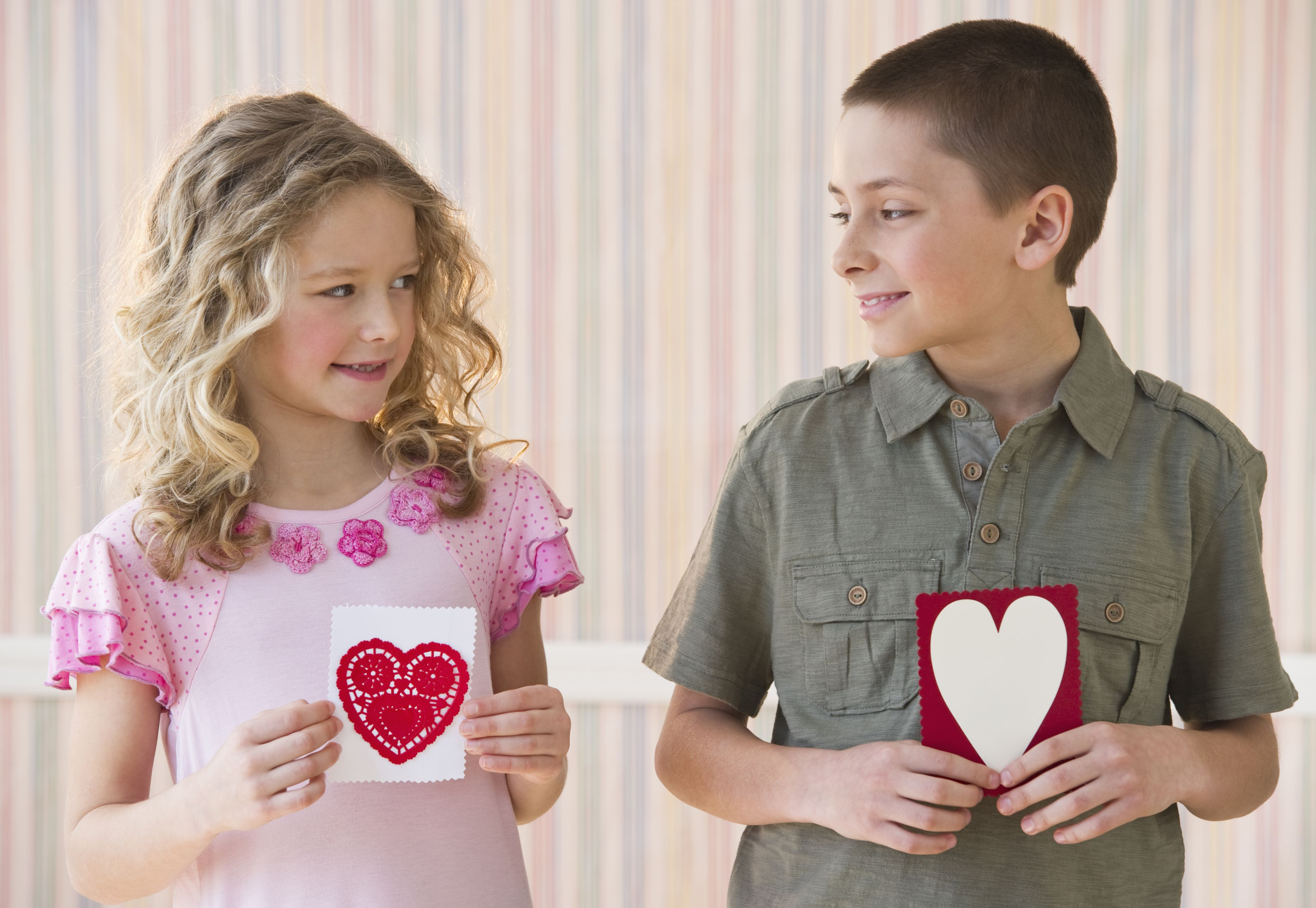 A girl and boy holding homemade valentines.