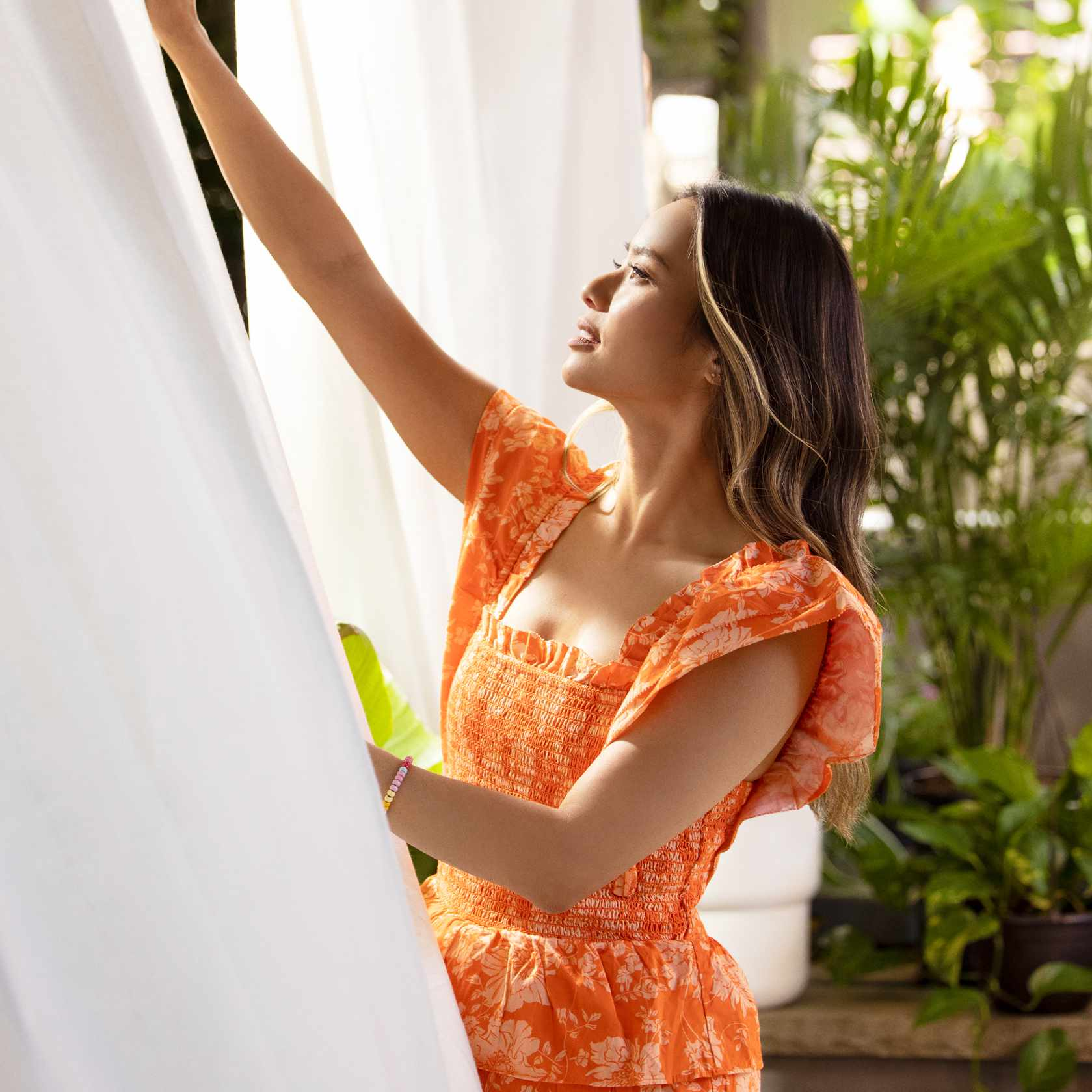 Jamie Chung arranges drapes in her Brooklyn outdoor space