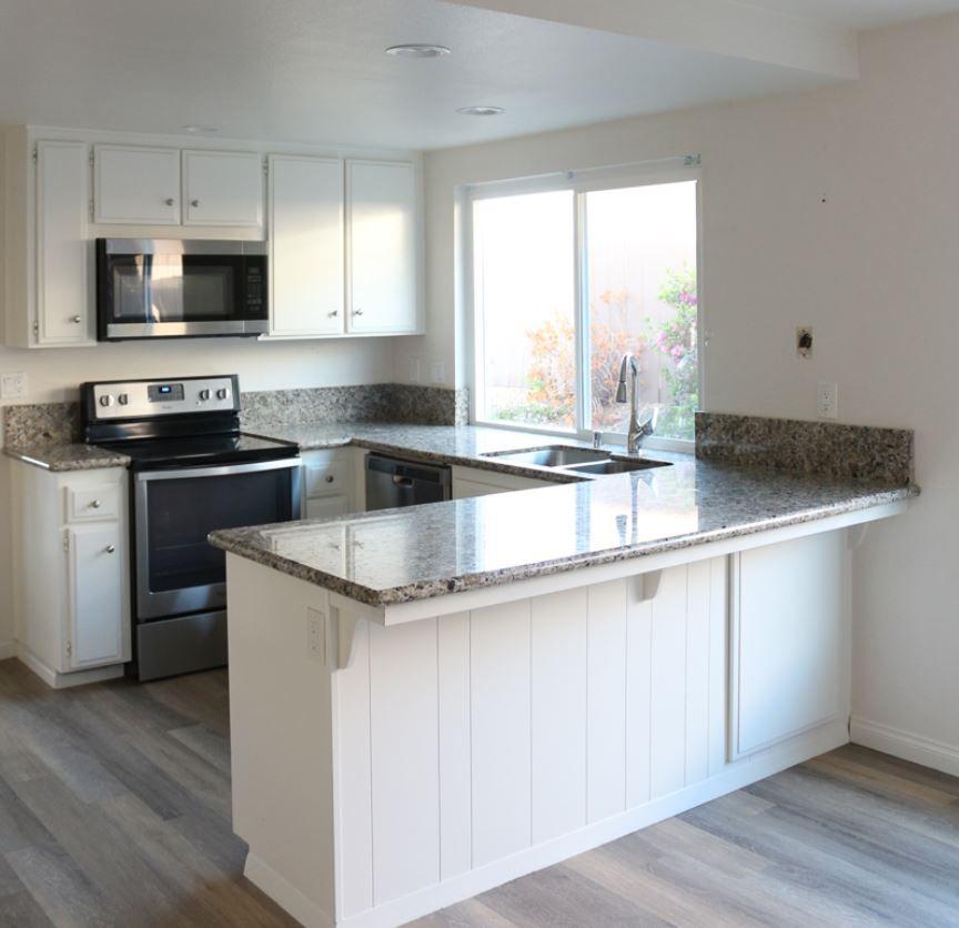 Cocina blanca con encimeras de granito gris