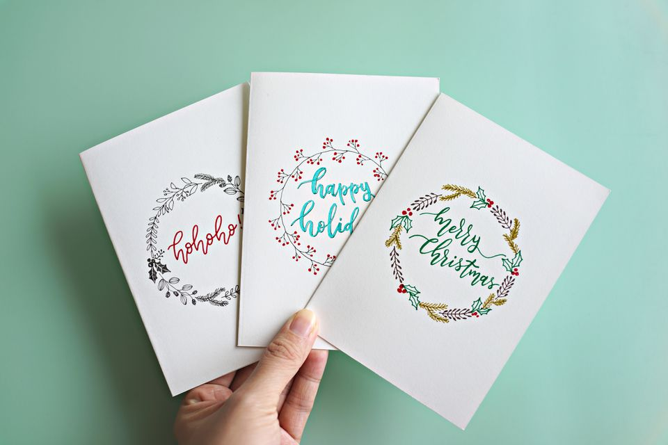 A hand holding three holiday greeting cards