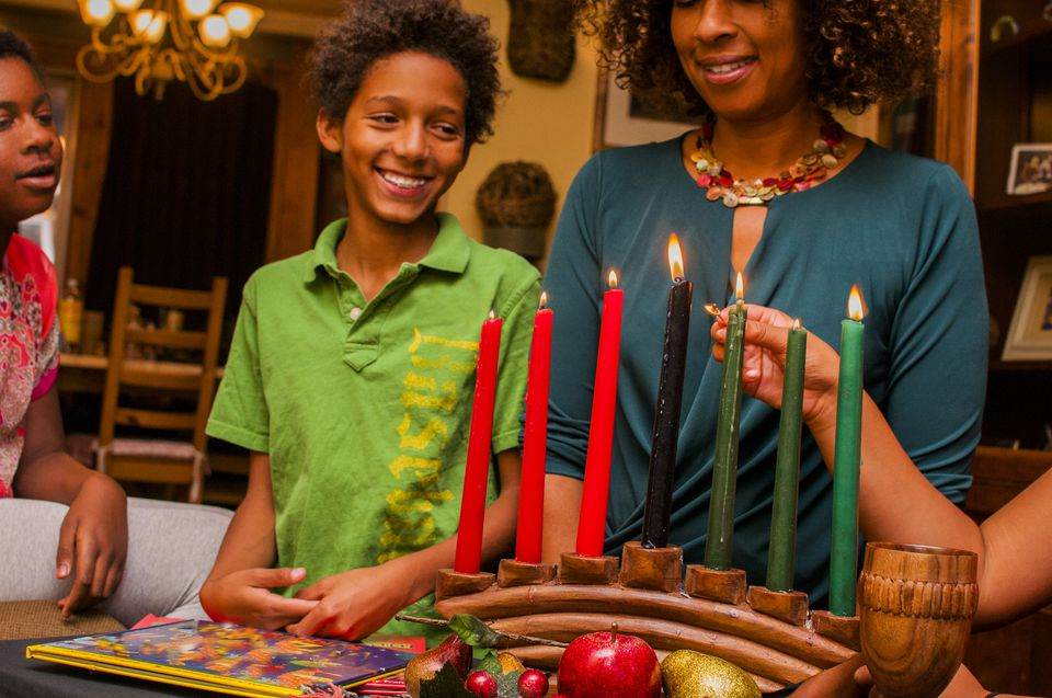 Family lighting kinara candles, celebrating Kwanzaa