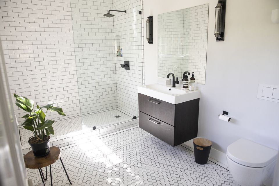 White tiled bathroom with a plant