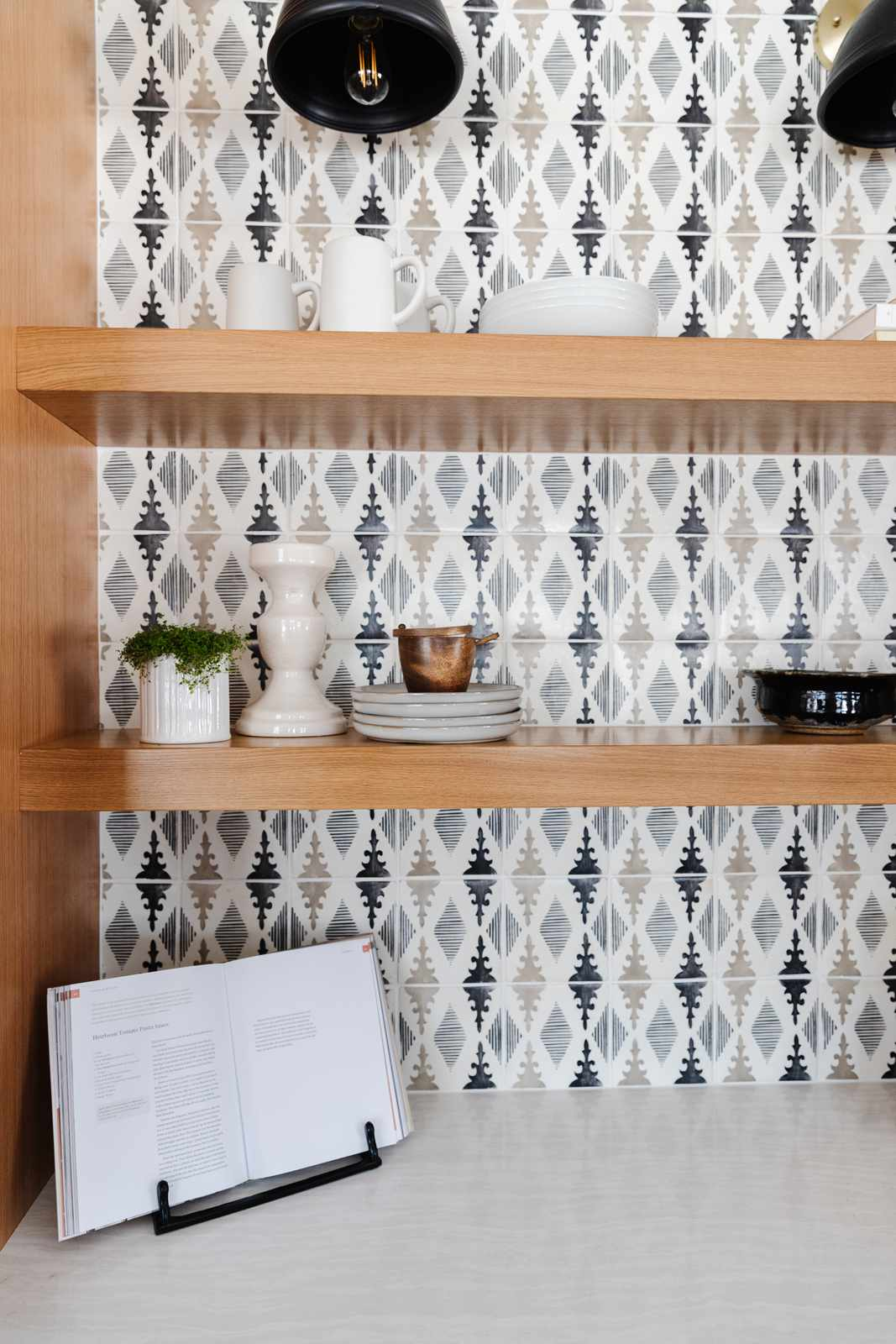 kitchen counter with floating shelves and backsplash, one cookbook propped open for display