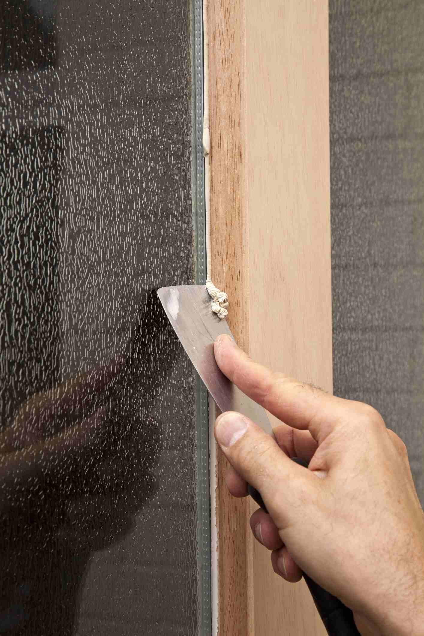 A hand removing glazier putty with a scraper