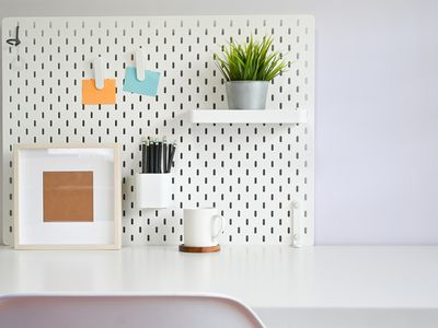 A white pegboard with a plant and pens on a desk.
