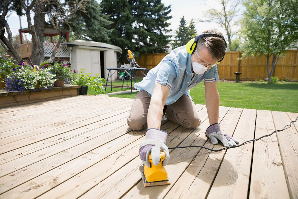 Man sanding wooden deck
