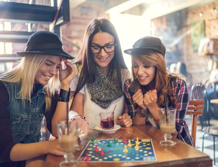 Happy friends playing cross and section game in a cafe.