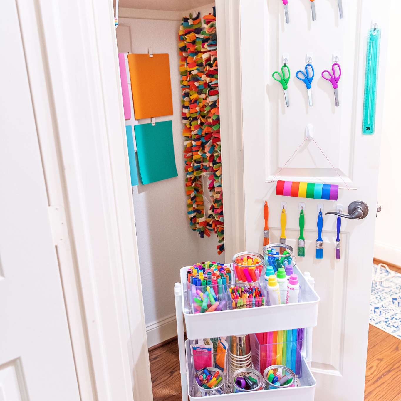 craft supplies stores on hooks behind a closet door and in a cart