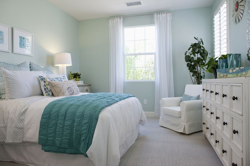 Bright bedroom with pale green walls and white furniture