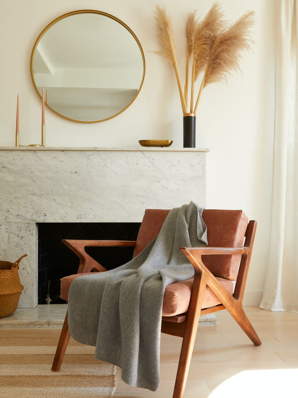 round mirror above a marble fireplace with a earthy color chair
