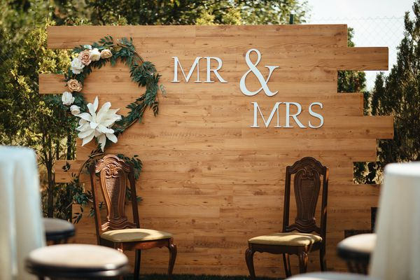 Mr & Mrs sign with chairs for newlyweds at wedding reception.