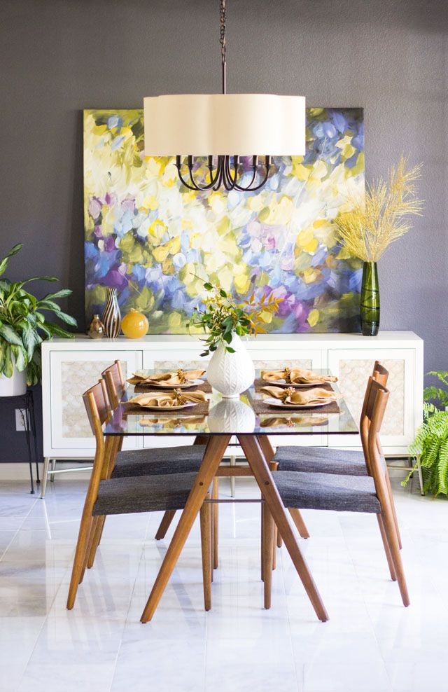 large painting leaning on sideboard