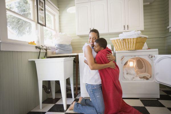 Mother hugging son wearing towel