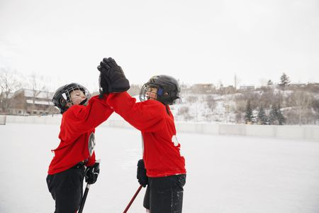 ice hockey players giving high five on rink