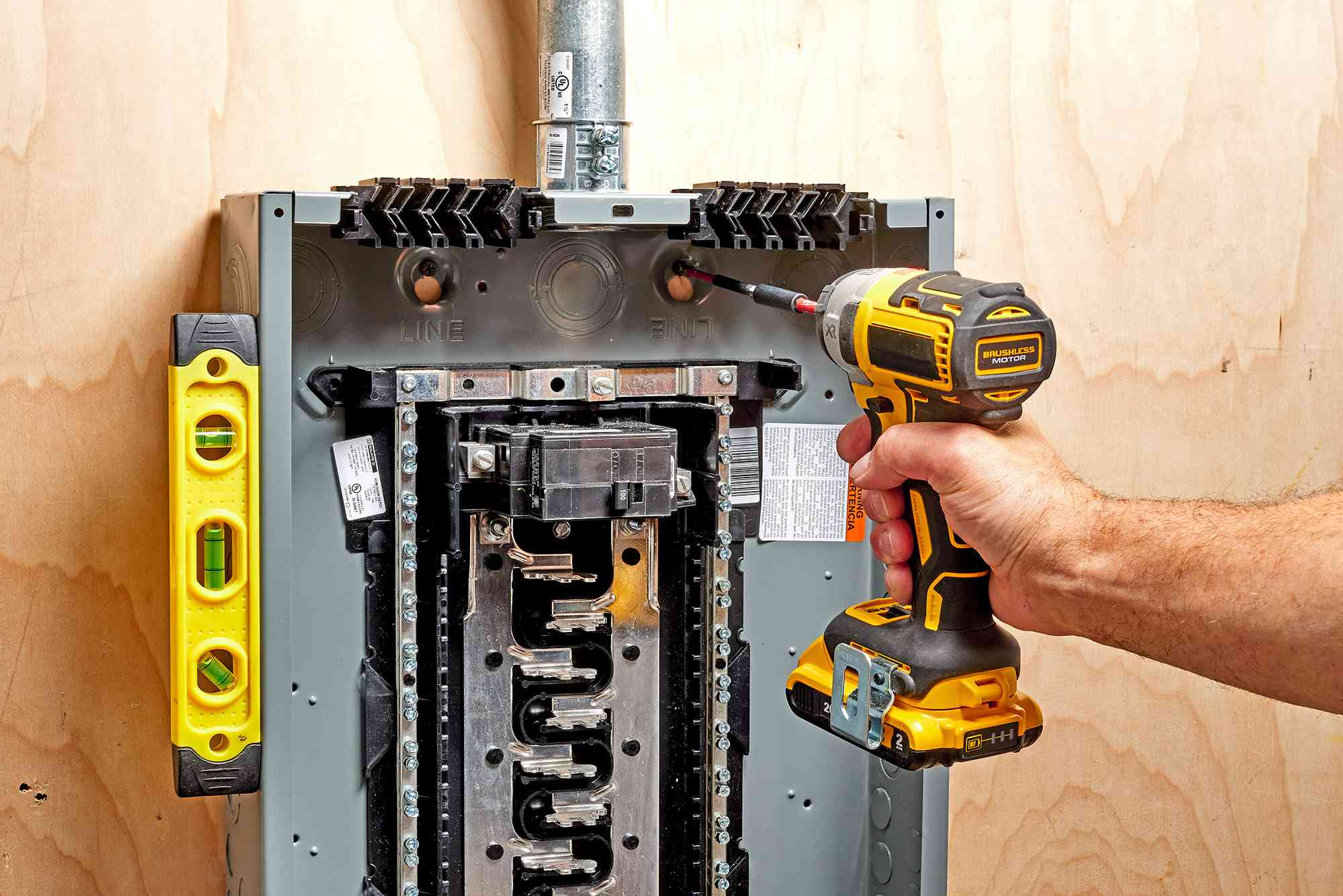 Electric drill drilling extra holes in back of electric panel wall to accommodate installation