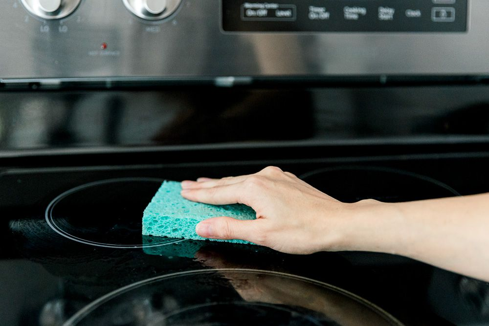 cleaning the cooktop with a sponge