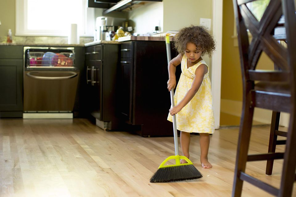 Girl sweeping kitchen floor