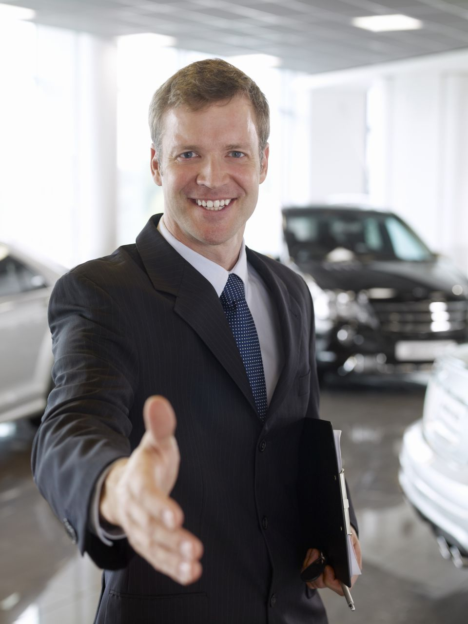 Car salesman greeting customers