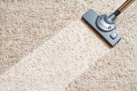 A vacuum pushed over carpet