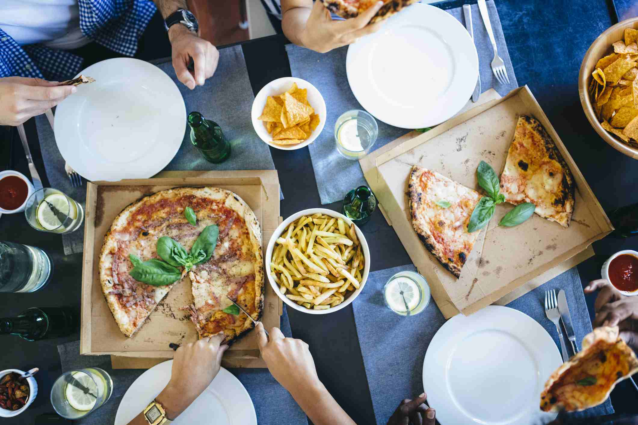 Friends sharing pizza and french fries.