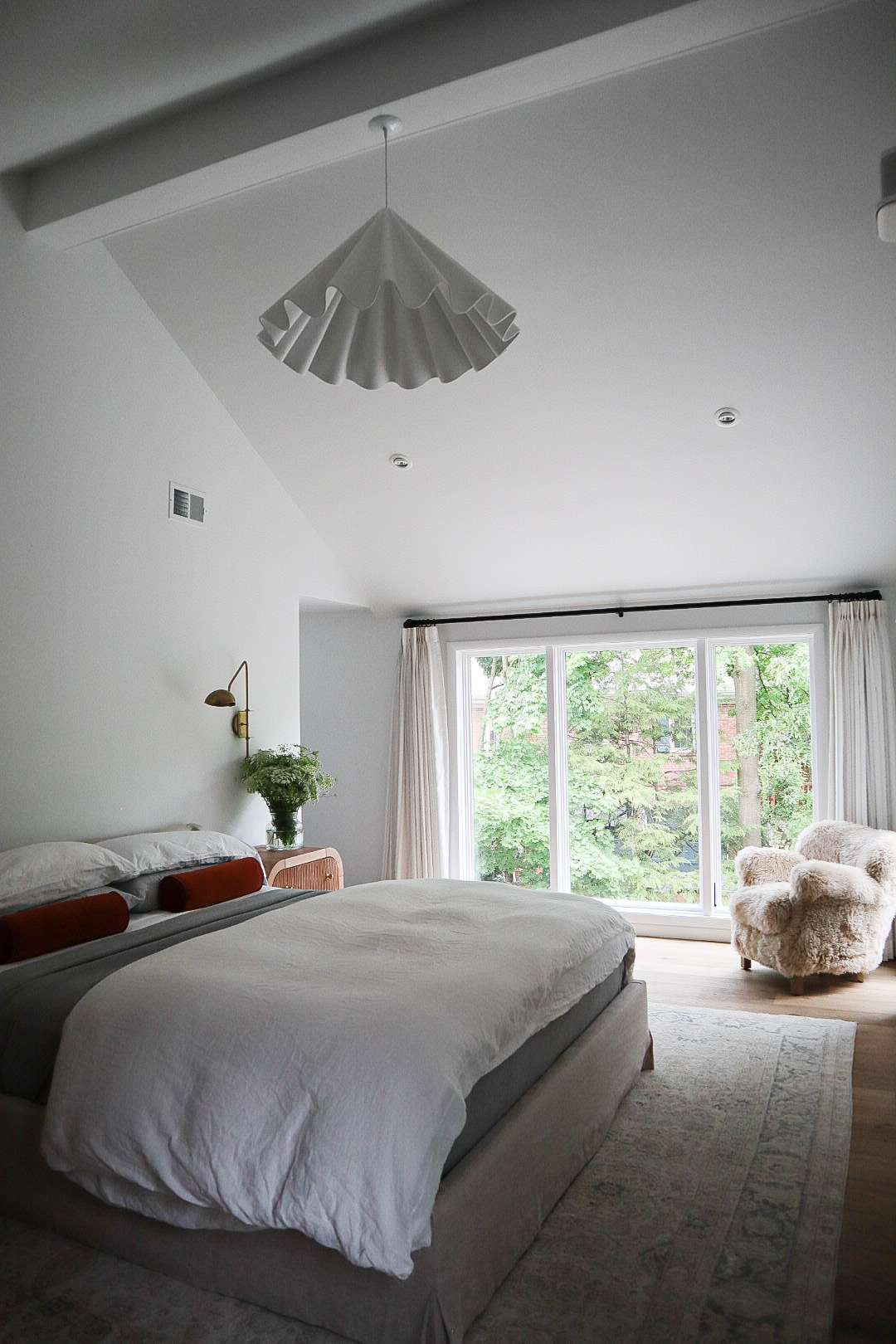 The bedroom in Molly & Fritz's Shaker Heights home features floor-to-ceiling windows that overlook the backyard and pool