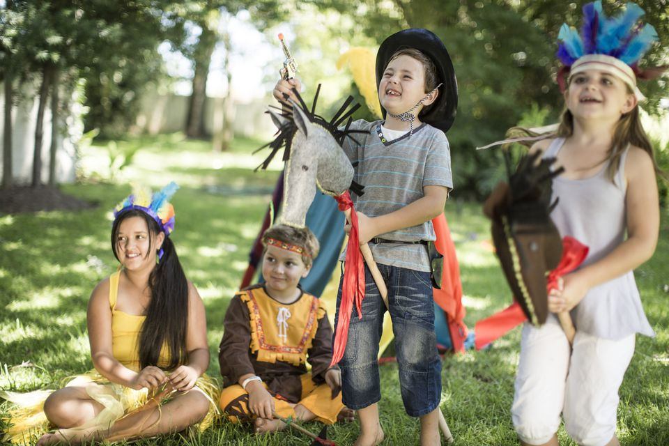 Kids in a garden playing Cowboys and Indians