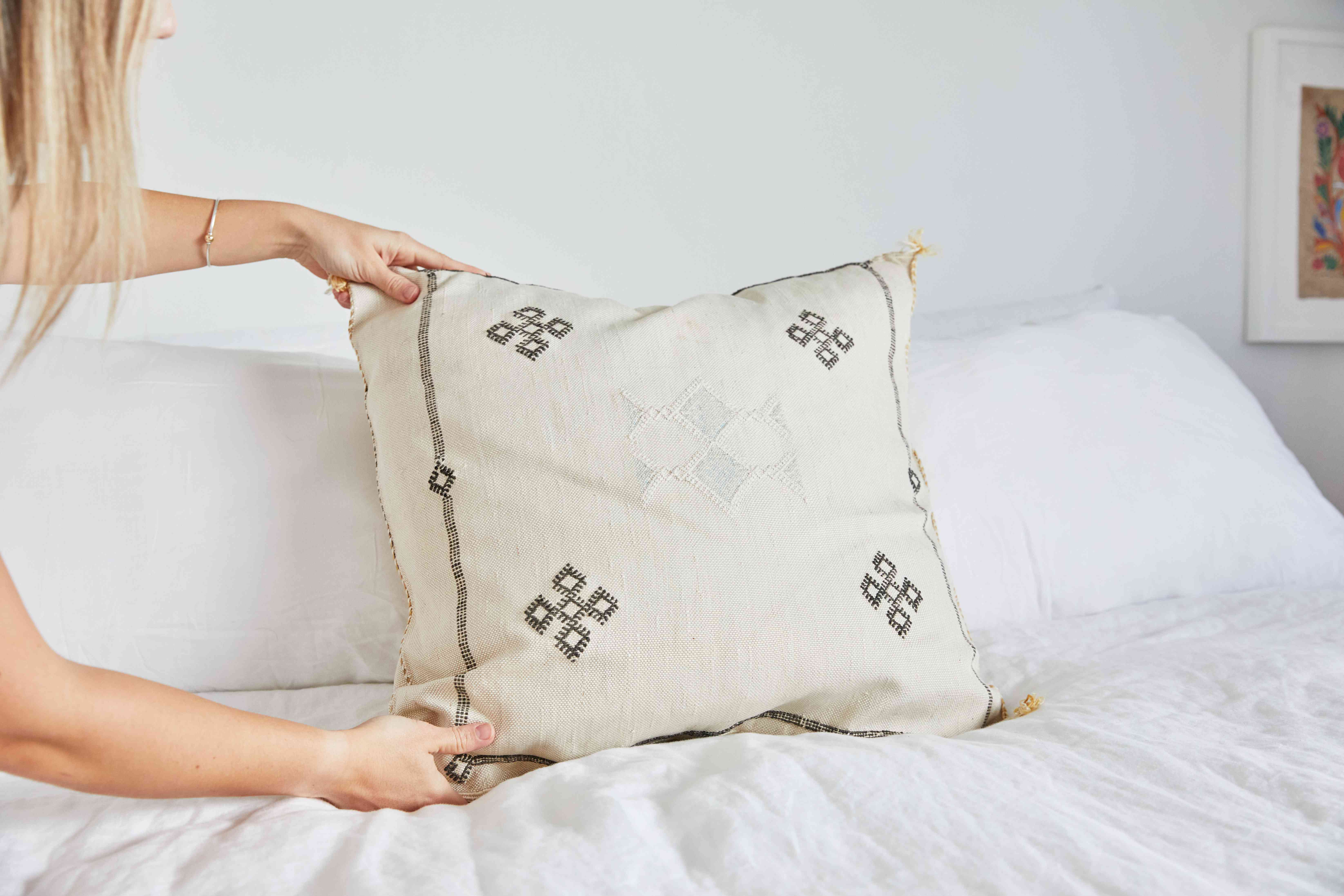 person placing a pillow on a made bed