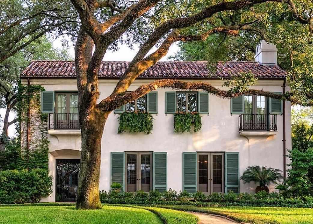 Casa de estuco con persianas verdes