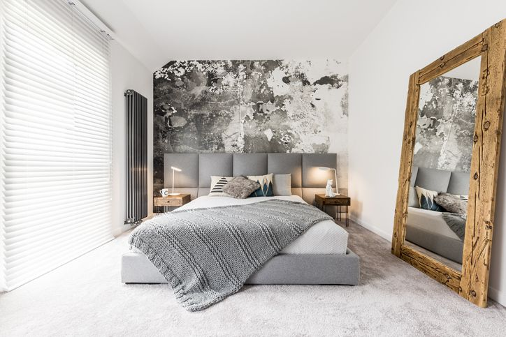 gray and white bedroom with large wooden mirror