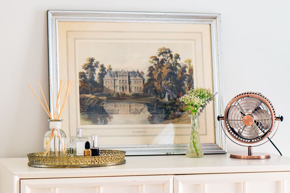White framed art leaning on dresser top with small fan and gold metal tray with diffuser and perfume bottles