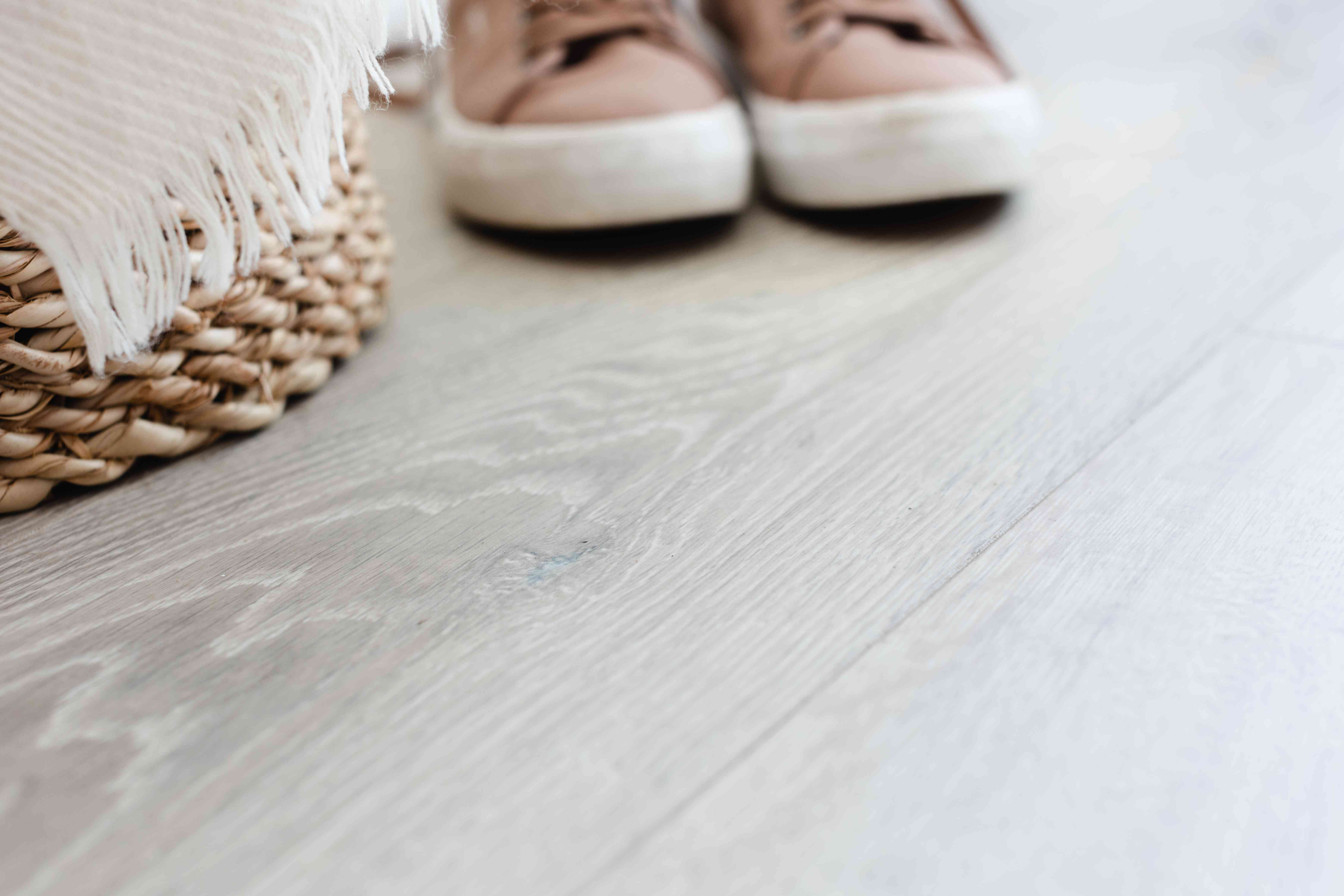 Laminate flooring of light stained wood with basket and shoes on top closeup