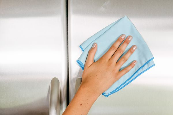 Blue microfiber cloth cleaning metal on outside of refrigerator doors